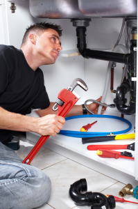 a strong service tech prepares to remove the drain seal from a leaky sink